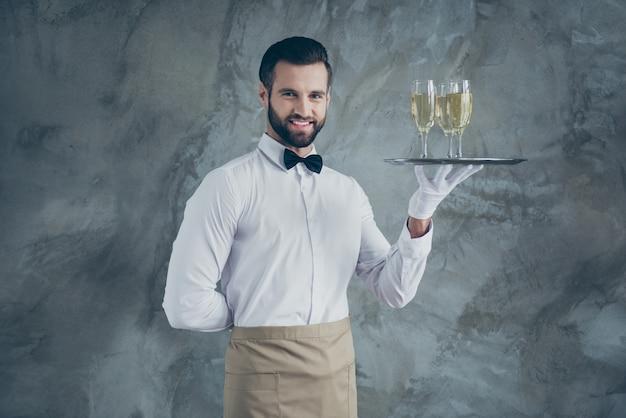 Foto des attraktiven gutaussehenden mannes mit der hand hinter seinem rücken lächelnd zahnig mit borste auf gesicht, das tablett mit gläsern der champagner lokalisierten grauen betonwand hält