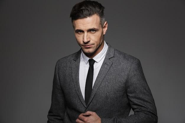 Foto des attraktiven jungen mannes 30s, der geschäftsanzug und krawatte mit ernstem blick trägt, lokalisiert über graue wand