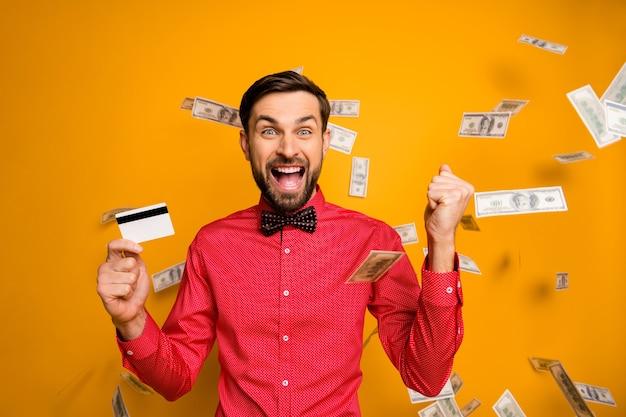 Foto des attraktiven lustigen kerls halten plastikkreditkarte reiche person geld dollars fallen überall schreiend tragen trendige rote hemd fliege kleidung