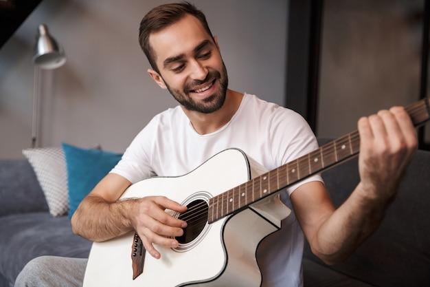 Foto des attraktiven mannes 30s, der lässiges t-shirt trägt, das akustische gitarre spielt, während auf sofa in wohnung sitzt