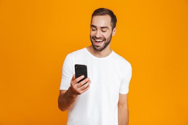 Foto des attraktiven mannes 30s in der freizeitkleidung, die smartphone lächelt und hält, lokalisiert