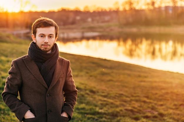 Foto des attraktiven mannes mit braunem haar und bart, die im braunen mantel tragen. warme sonnenuntergangsfarben.