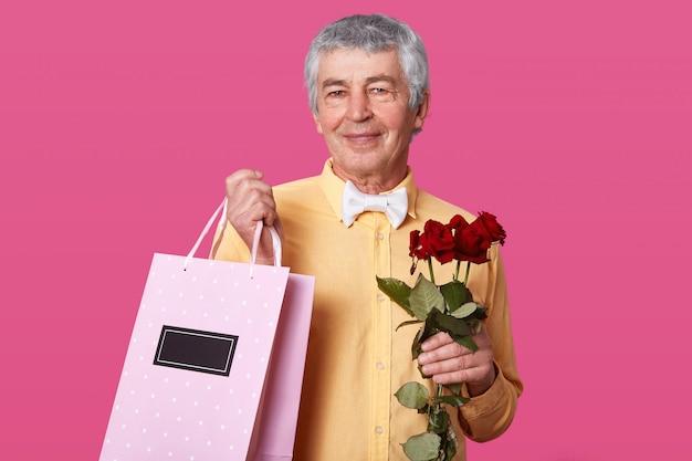 Foto des attraktiven reifen mannes mit angenehmem gesichtsausdruck, gekleidet in gelbes hemd mit weißer fliege, trägt rosa tasche mit geschenk und rosen, will frau mit hochzeitstag gratulieren.