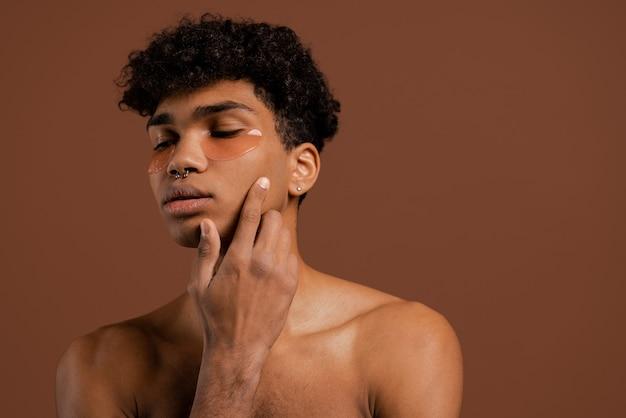 Foto des attraktiven schwarzen mannes mit durchdringendem blick nach unten und berührt sein gesicht mit augenklappen auf. nackter torso, isolierter brauner farbhintergrund.