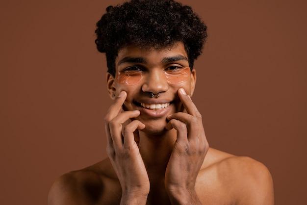 Foto des attraktiven schwarzen mannes mit piercing und augenklappen auf blicken auf kamera mit lächeln und berührt sein gesicht. nackter torso, isolierter brauner farbhintergrund.