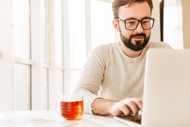 Foto des attraktiven unrasierten mannes, der brillen trägt, die tee aus glas trinken, während sie arbeiten oder im internet auf laptop im büro surfen