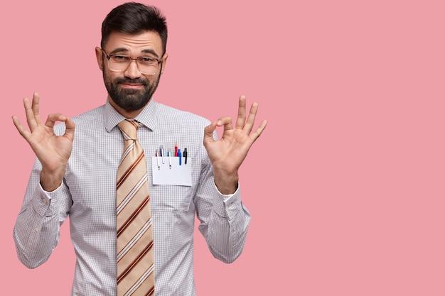 Foto des attraktiven unrasierten mannes macht okay geste mit beiden händen, gekleidet in formelles outfit