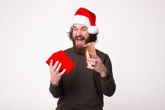 Foto des aufgeregten bärtigen mannes, der weihnachtsmannhut trägt und geschenkbox betrachtet
