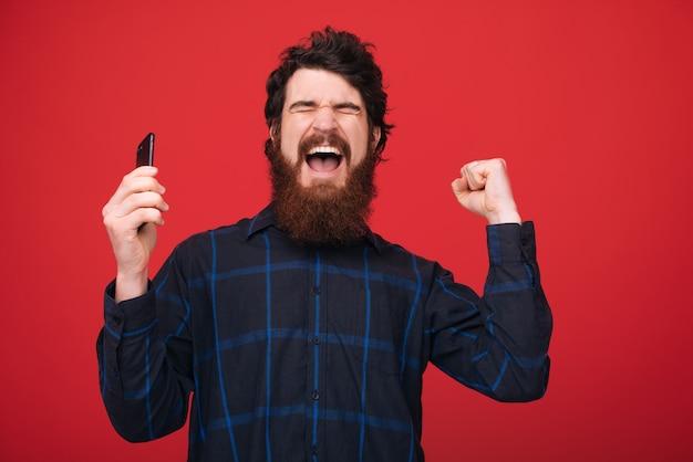Foto des aufgeregten kerls, der handy hält und mit risd hände und geschlossenen augen über roter wand feiert