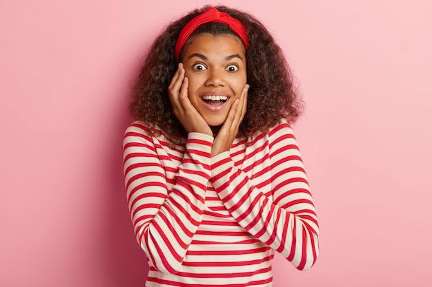 Foto des aufgeregten teenager-mädchens mit dem lockigen haar, das im gestreiften roten pullover aufwirft