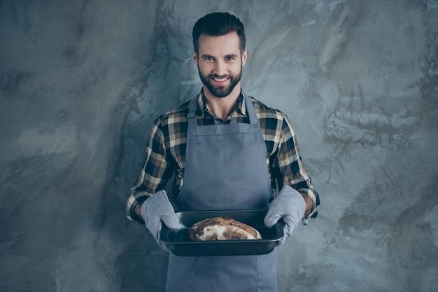 Foto des bärtigen guten fröhlichen professionellen kochs, der das brot fertig gekocht hat und dies serviert, um isolierte graue farbwandbetonwand zu tischen