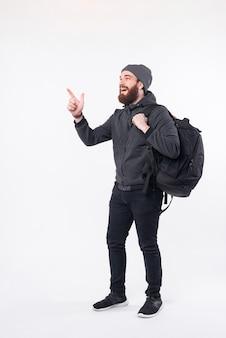 Foto des bärtigen hipster-mannes, der rucksack trägt und weg an die ecke zeigt
