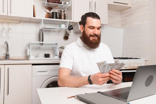 Foto des bärtigen mannes, der vor laptop nach hause sitzt und geld zählt