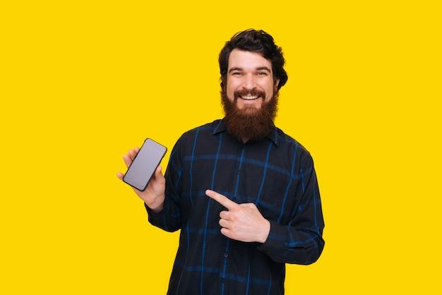 Foto des bärtigen mannes mit dem zahnigen lächeln, das auf bildschirm des smaprtphone zeigt, der über gelber wand steht