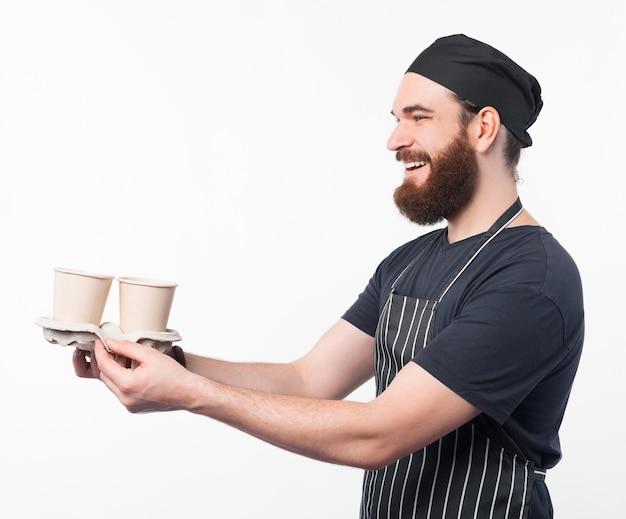 Foto des barista-mannes, der jemandem zwei kaffee gibt