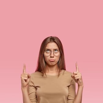 Foto des beeindruckten weiblichen modells fühlt sich unglücklich
