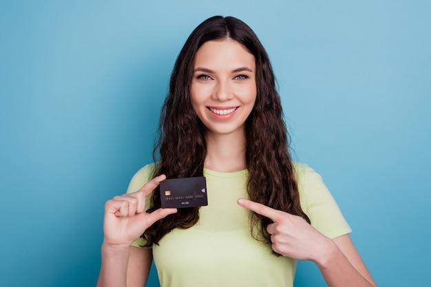Foto des beratermädchens, das neue debitkarte zeigt, zeigt zeigefingerseite auf blauem hintergrund an