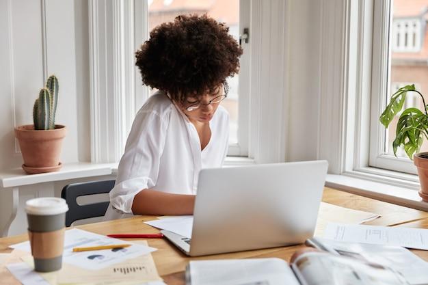 Foto des beschäftigten dunkelhäutigen managers spricht mit dem kunden über handy, schreibt einige informationen in papierform, sitzt am desktop und notiert text, laptop-computer