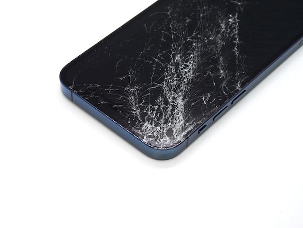 Foto des blauen smartphones mit gebrochener beschädigter anzeige. modernes smartphone mit beschädigtem glasbildschirm auf weißer oberfläche. gerät muss repariert werden.