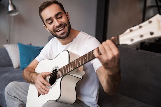 Foto des brünetten mannes 30s, der lässiges t-shirt trägt, das akustische gitarre spielt, während auf sofa in der wohnung sitzt