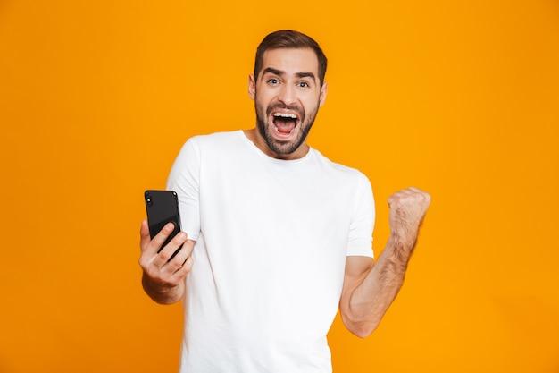 Foto des brünetten mannes 30s in der freizeitkleidung, die smartphone schreit und hält, lokalisiert