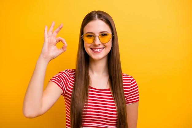 Foto des charmanten hübschen jungen mädchens mit langer frisur, das lächelt, die hand zeigt, dass okey die neue aktualisierte produktlinie genehmigt, die sonnenspezifikationen trägt, gestreiftes weißes rotes hemd, leuchtend gelber farbhintergrund