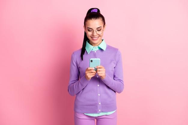 Foto des charmanten mädchens mit telefon-look-bildschirm tragen spezifikationen lila strickjacke isoliert rosa hintergrund