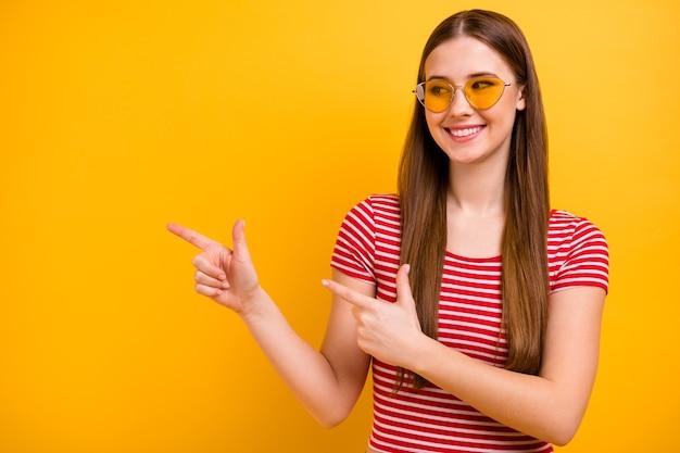Foto des charmanten, schönen jungen mädchens, das lächelt und mit den fingern zeigt, dass der leere raum vorgeschlagen wird