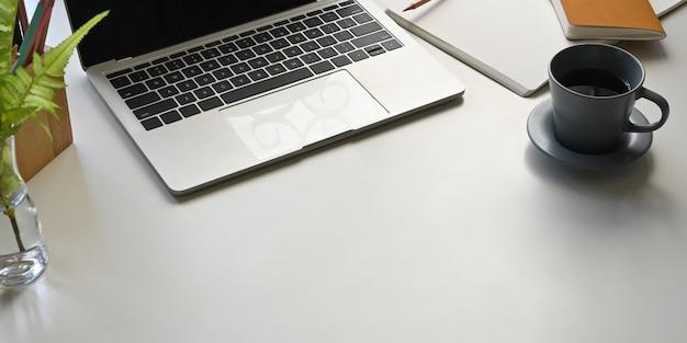 Foto des computer-laptops, der auf weißen schreibtisch setzt und von notizbuch, tagebuch, topfpflanze, kaffeetasse und stifthalter umgeben ist. ordentliches arbeitsbereichskonzept.