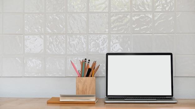 Foto des computer-laptops mit weißem leerem bildschirm, der mit hölzernem bleistifthalter und büchern auf dem modernen holztisch mit weißer keramikziegelfliesenwand zusammensetzt