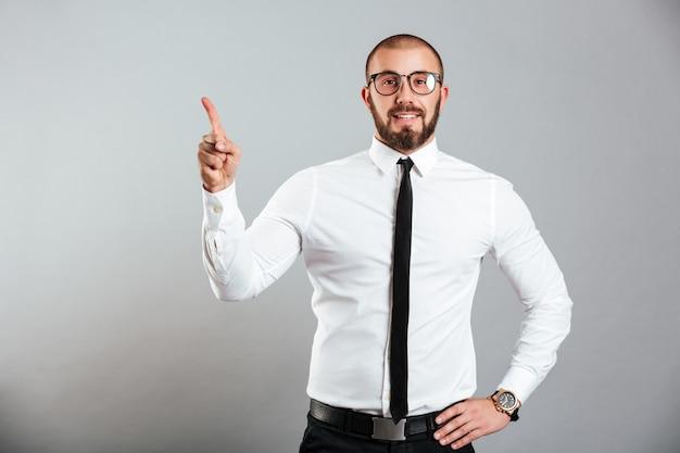 Foto des ehrgeizigen kaukasischen mannes im weißen hemd und in den brillen, die auf kamera lächeln und finger nach oben auf kopienraum zeigen, lokalisiert über graue wand