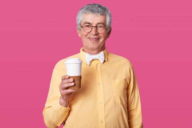 Foto des eleganten senioren, der pappbecher kaffee hält, bereit, heißes getränk zu trinken, gekleidet in formelles hemd und fliege, hat treffen, modelle auf rosiger studiowand mit leerem raum für ihre werbung.