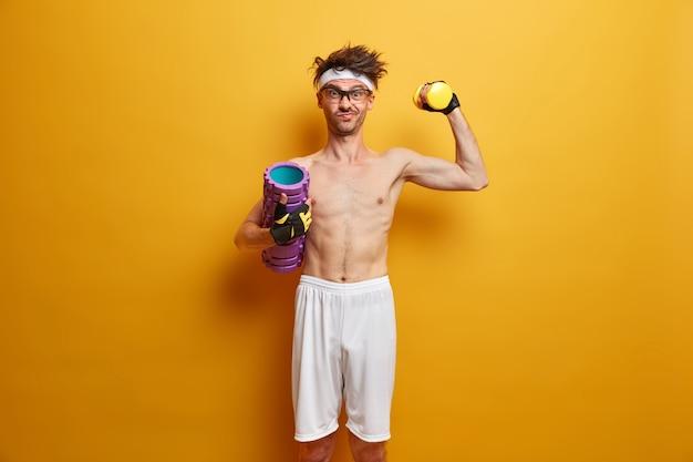 Foto des entschlossenen athletischen mannes hebt hantel, posiert mit schaumstoffrolle, hat das ziel, stark zu sein, genießt übungen im fitnessstudio, isoliert auf gelber wand. menschen-, gesundheits- und fitnesskonzept. gesunder lebensstil