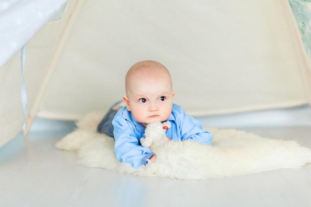 Foto des entzückenden babyjungen, der auf dem boden in ihrem kinderzimmer unter dem zelt liegt