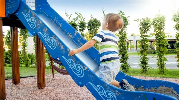 Foto des entzückenden lächelnden jungen, der auf folie klettert und reitet. aktives kind, das spaß hat und im park spielt