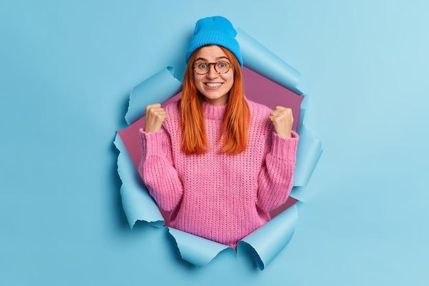 Foto des erfreuten rothaarigen tausendjährigen mädchens hebt geballte fäuste feiert erfolglächeln trägt breit blauen hut und rosa gestrickter pullover bricht durch papierloch