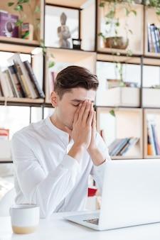 Foto des ernsten mannes, der im weißen hemd unter verwendung der laptop-computer gekleidet wird. coworking. augen geschlossen.