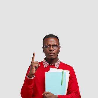 Foto des ernsthaften dunkelhäutigen mannes hat mürrischen ausdruck, zeigt oben, gekleidet in roten pullover mit hemd, hält notizbuch mit stift