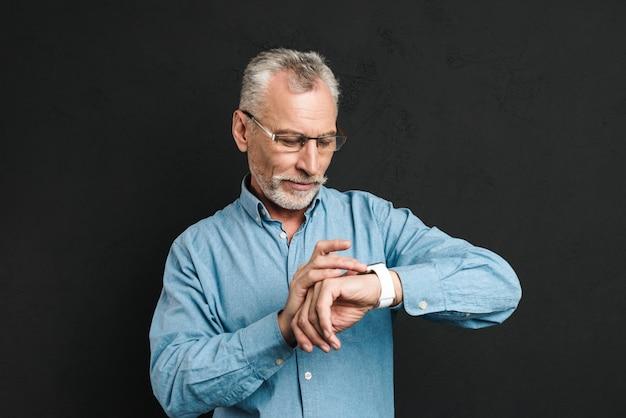 Foto des ernsthaften herrn 60s mit grauem haar, das brillen trägt, die seine armbanduhr mit spannung betrachten, lokalisiert über schwarzer wand