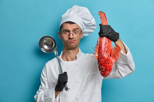 Foto des ernsthaften professionellen kochs hält schöpflöffel und fisch, bereitet gourmet-meeresfrüchtegericht zu, trägt weiße uniform, schwarze handschuhe, kocht suppe des roten basses