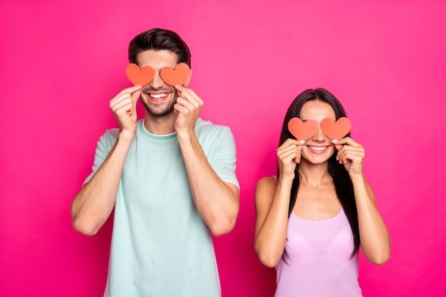 Foto des erstaunlichen kerls und der dame, die kleine papierherzen in den händen hält, die augen verstecken, die sich gegenseitig zum abschlussball des studenten einladen tragen lässiges outfit isolierten rosa farbhintergrund