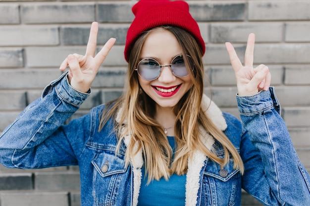 Foto des erstaunlichen mädchens in runden gläsern, die glück auf ziegelmauer ausdrücken. außenaufnahme der verträumten weißen frau im roten hut und in der jeansjacke lachend