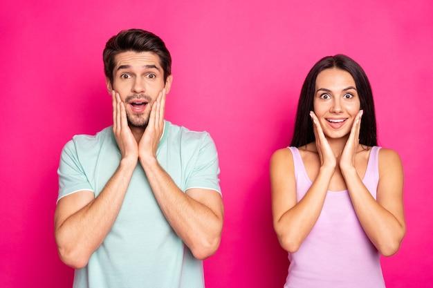 Foto des erstaunlichen paares kerl und dame, die auf niedrige einkaufspreise schauen, die etwas tragen, tragen lässige stilvolle kleidung lokalisierten lebendigen rosa farbhintergrund