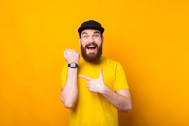 Foto des erstaunten bärtigen hipster-mannes im gelben t-shirt, das auf seine neue smartwatch zeigt