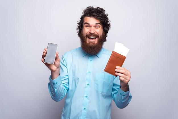 Foto des erstaunten mannes, der smartphonebildschirm und reisepass mit tickets zeigt