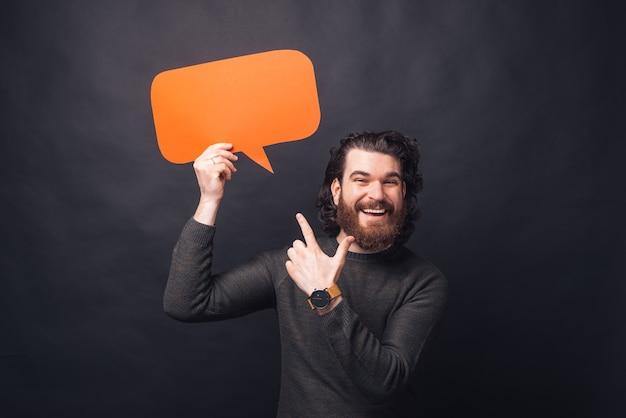 Foto des erstaunten mannes mit bart, der auf rote leere sprechblase zeigt