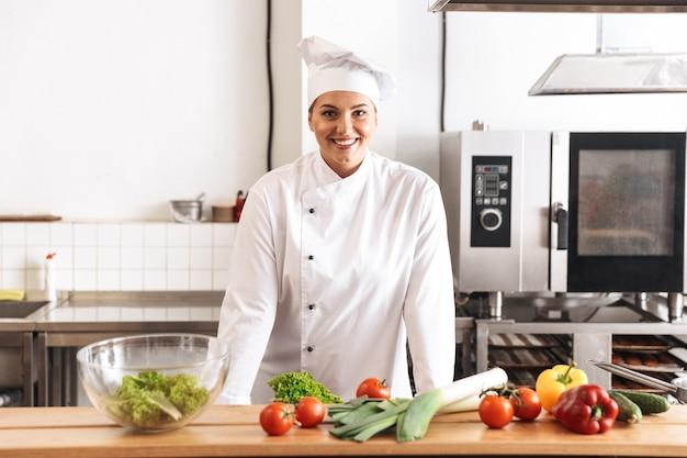 Foto des erwachsenen frauenkochs, der weiße einheitliche kochmahlzeit mit frischem gemüse trägt, in der küche am restaurant