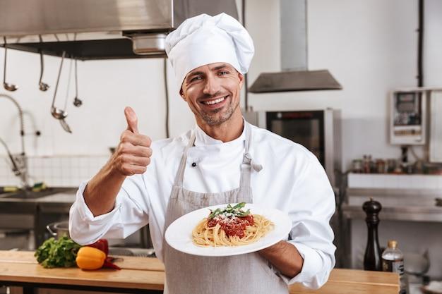 Foto des erwachsenen männlichen chefs in der weißen uniform, die platte mit mahlzeit hält