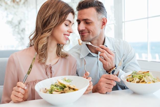 Foto des erwachsenen romantischen paares, das abendessen und das essen von salaten beim ausruhen im stadtcafé am sonnigen tag isst