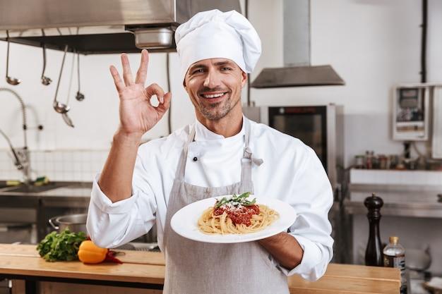 Foto des europäischen männlichen chefs in der weißen uniform, die platte mit mahlzeit hält